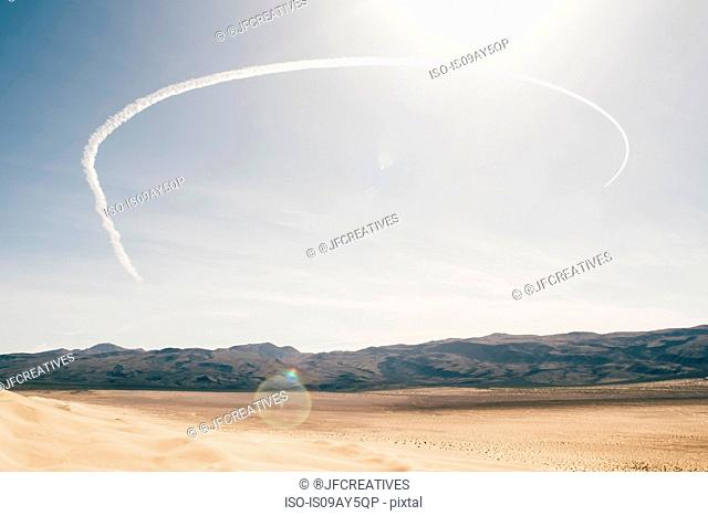 Desert landscape and semi circle vapour trail in blue sky, Olancha, California, USA