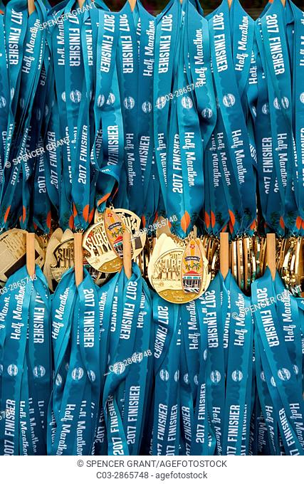 Gold medallions on neck ribbons for runners completing a half marathon in Huntington Beach, CA, are on display before the race