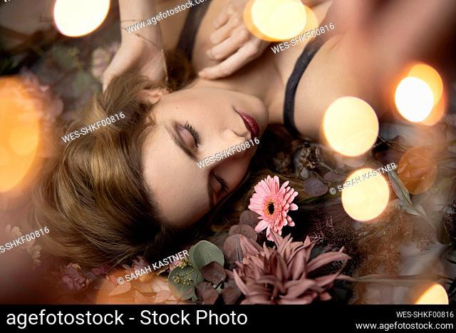 Beautiful woman lying on flowers, close up