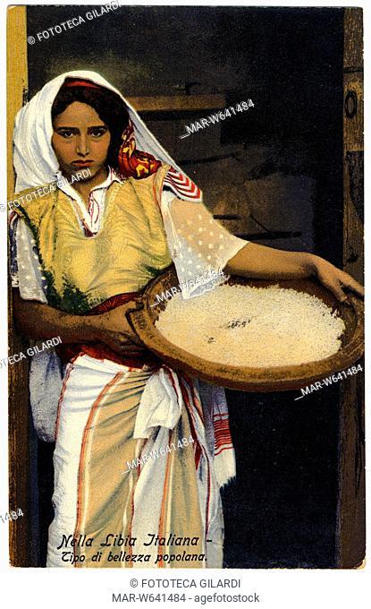 COLONIALISMO Libia italiana, tipo di bellezza popolana. La giovane donna tiene in mano, appoggiata al fianco, una grande ciotola colma di cous-cous