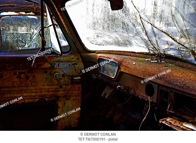 Rusty interior of abandoned truck with cracked windshield