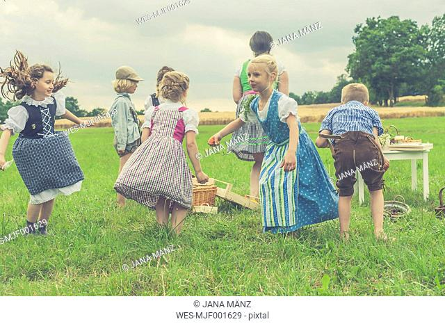 Germany, Saxony, children in traditonal clothes dancing on a meadow