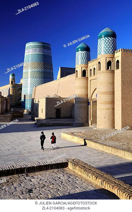 Schoolchildren walking by the Kuhna Ark fortress and the unfinished minaret Kalta Minor. Uzbekistan, Khorezm, Khiva, Itchan Kala (inner town)