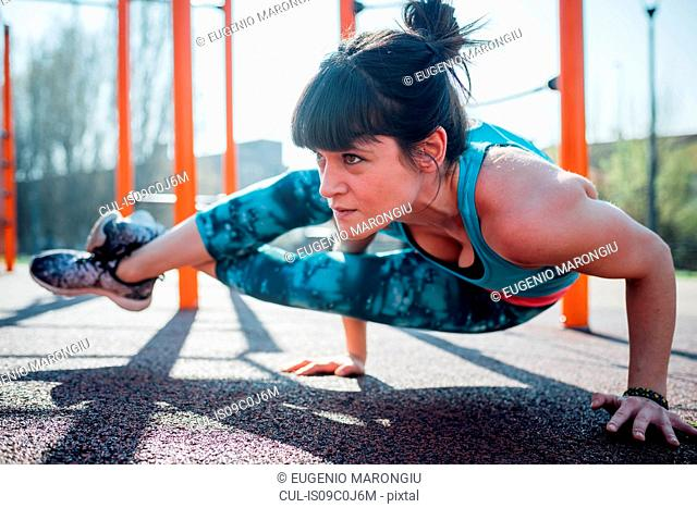 Calisthenics at outdoor gym, young woman with legs raised balancing on hands