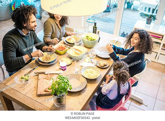 Happy family eating together pizza and pasta