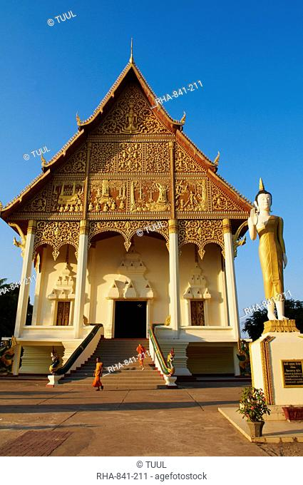 Statue of standing Buddha and monks, Pha That Luang temple, Vientiane, Laos, Indochina, Southeast Asia, Asia