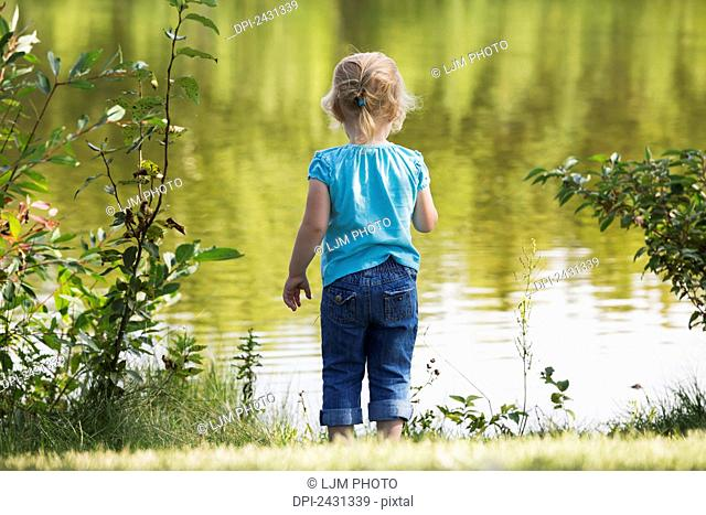 Young girl looking at water from the shore of a lake in a park; Edmonton, Alberta, Canada