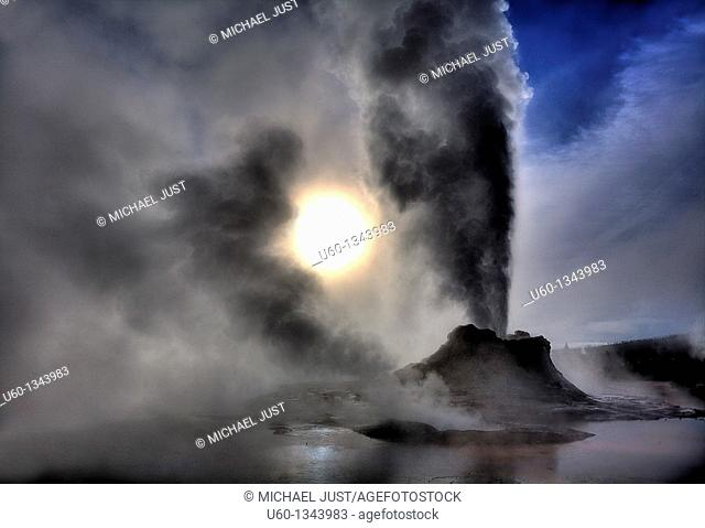 Castle Geyser erupts under a bright sky during winter at Yellowstone National Park