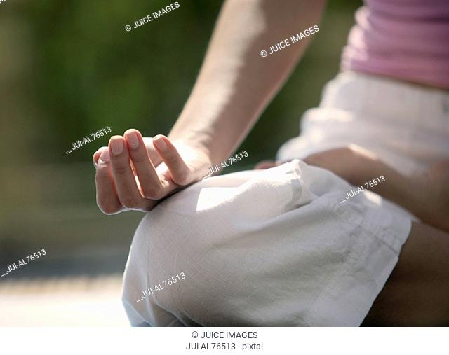 Close-up of a woman's hand placed on her knee as she meditates