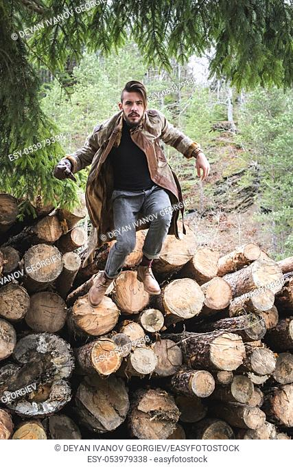 Young men on logs in the forest. Leather and jeans. Pine tree on top