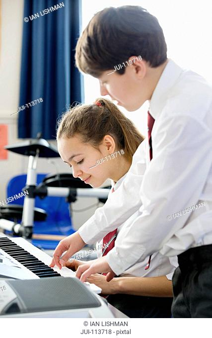 High school student helping classmate playing piano in music class