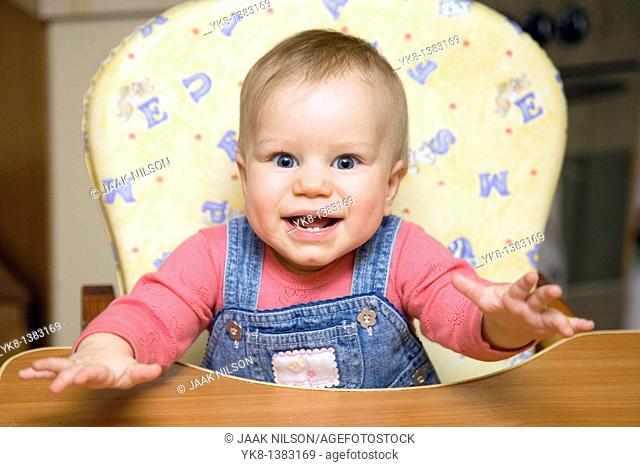 Happy Smiling Eight Month Old Infant Girl in High Chair
