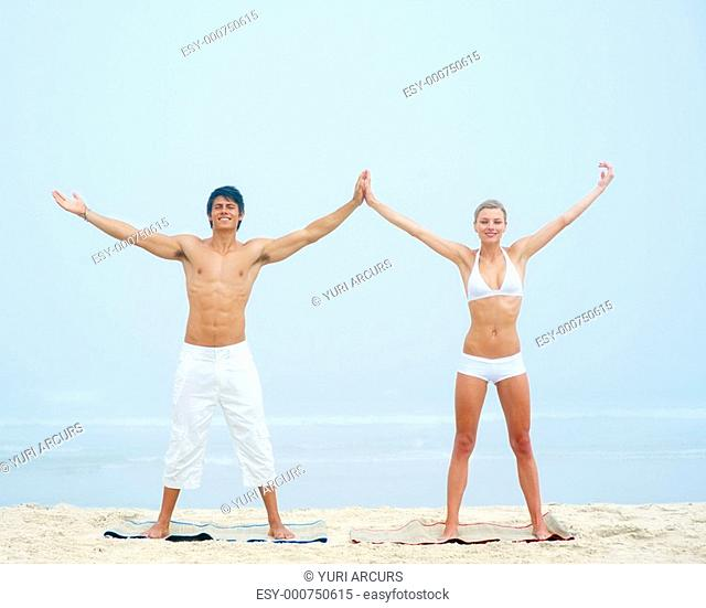 Portrait of a young man and woman stretching their hands and working out at the beach together