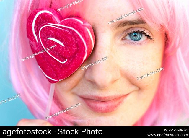 Portrait of young woman wearing pink wigwith heart-shaped lolly covering her eye