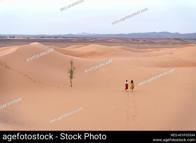 Two young women walking in Sahara Desert, Merzouga, Morocco