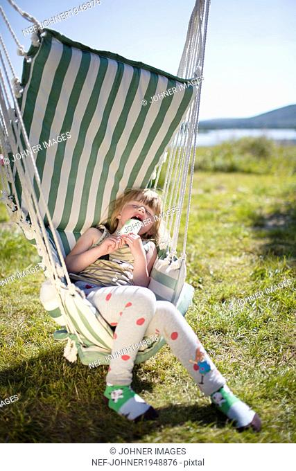 Girl sleeping on hammock with ice-cream, Kiruna, Lapland, Sweden
