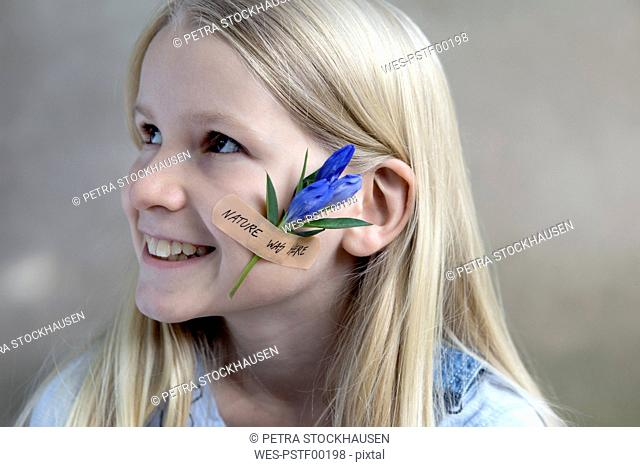 Portrait of smiling blond girl with flower head on her cheek