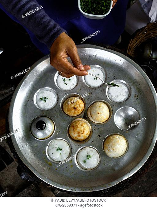 Sweet coconut pancakes made with rice flour & coconut milk, fried in a cast iron mold, Vientiane, Laos