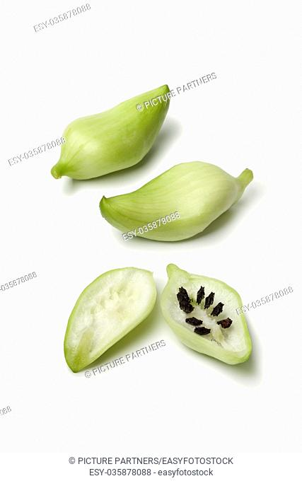 Whole and half green heirloom wild cucumber with black seeds on white background