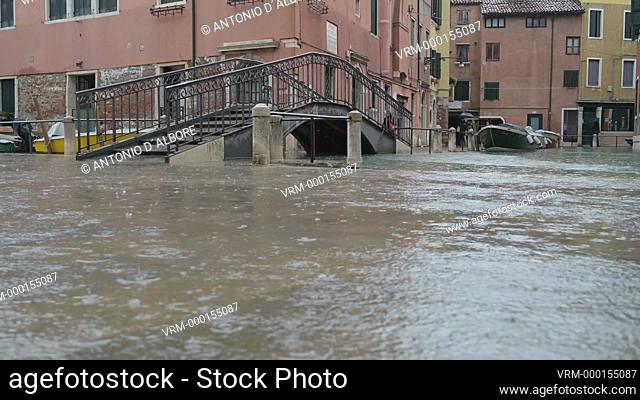 A local resident crossing a pedestrian bridge in Castello Quarter, during during the so called 'acqua alta' high tide. Venezia. Italy