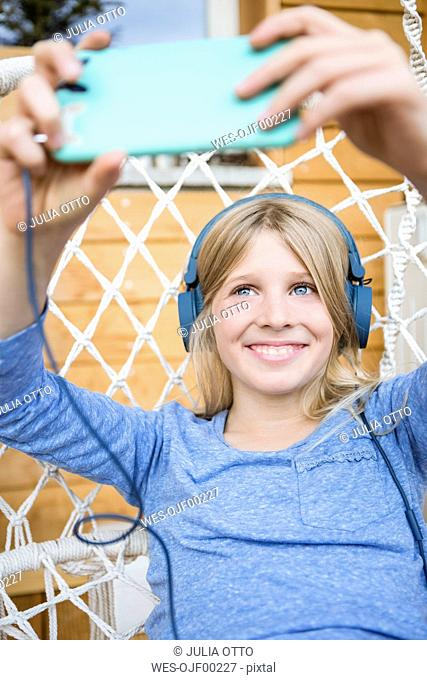 Portrait of laughing girl with headphones taking taking selfie with smartphone in a hanging chair