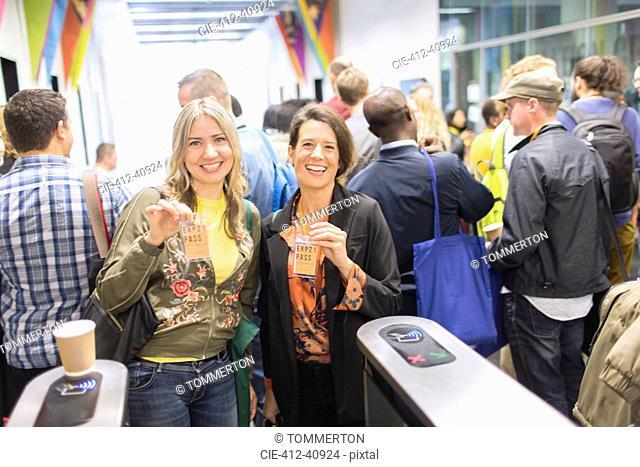 Portrait smiling, confident women showing lanyard conference passes
