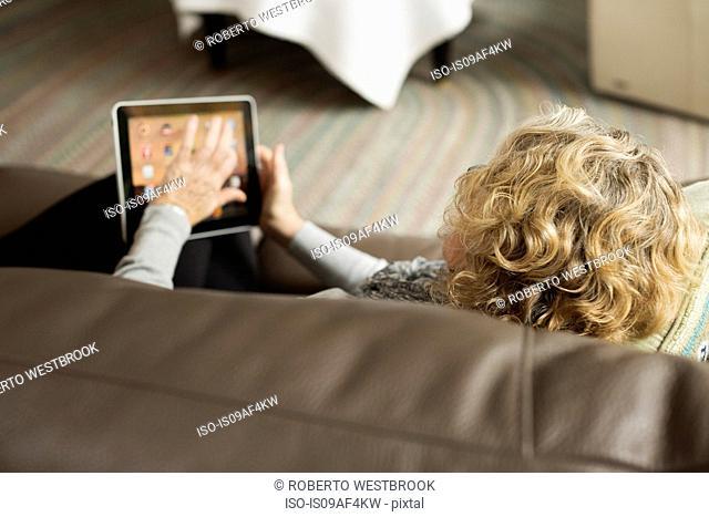 Senior woman reclining on sofa with digital tablet