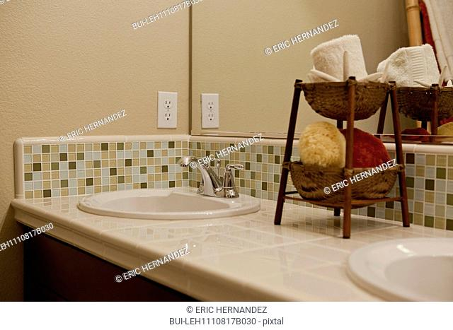 Close-up of tiled counter and washbasin in the bathroom at home; California; USA
