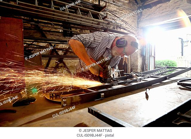 Blacksmith grinding metal on workbench in blacksmiths shop