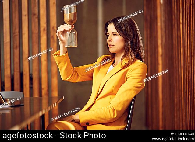 Businesswoman wearing yellow suit sitting at desk in office holding hourglass