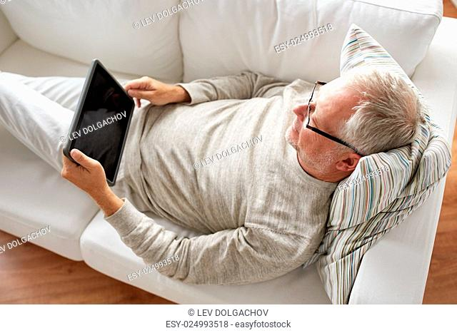 technology, people and lifestyle concept - senior man with black blank tablet pc computer screen lying on sofa at home