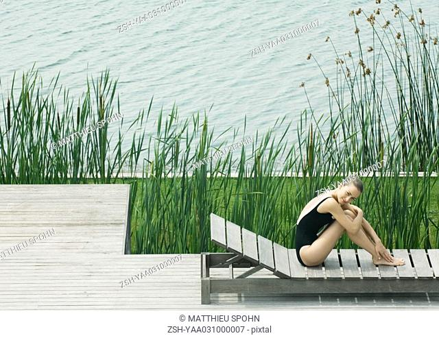 Young woman sitting on lounge chair