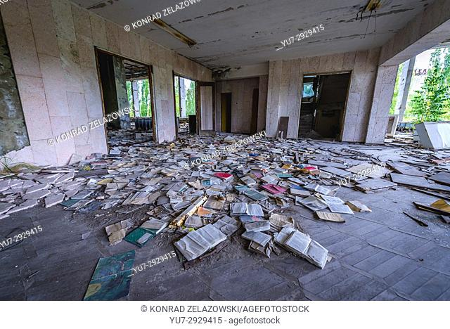 Books on the floor of Palace of Culture Energetik in Pripyat ghost city of Chernobyl Nuclear Power Plant Zone of Alienation in Ukraine