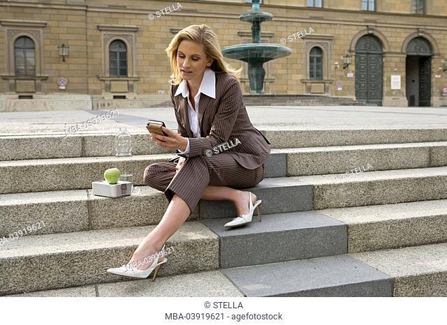 businesswoman, sit, stone stairway, lunchbox, apple, water bottle, iPod