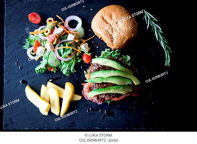 Overhead view of hamburger with avocado, side salad and chips on slate