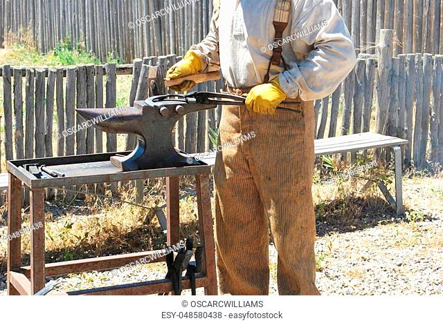 Male farrier working on a horseshoe outdoors
