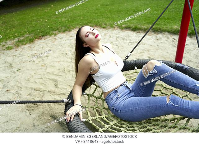 Young woman relaxing on swing. Munich, Germany