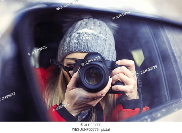 Wing mirror with mirror image of woman taking picture of herself, close-up