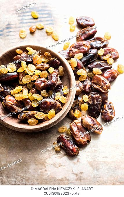 Dried dates and yellow raisins in bowl, close-up