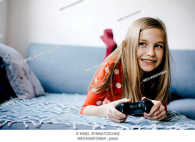 Happy girl playing video game at home