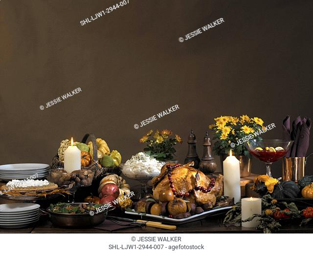 FALL THEME FOOD: Bountiful fall feast, Thanksgiving set up with brown backdrop, turkey with cranberry garland, mum plants , basket of gourds, candles