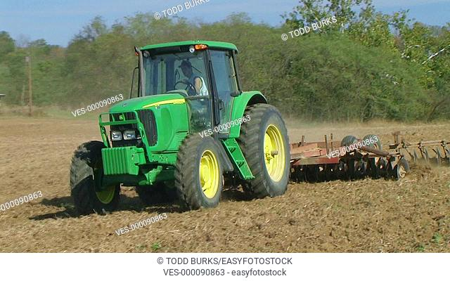 Tractor discing field with disc harrows