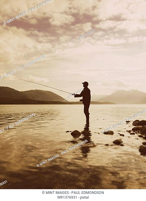Silhouette of a man flyfishing in calm waters on the Waschusett inlet in Glacier Bay national park in Alaska