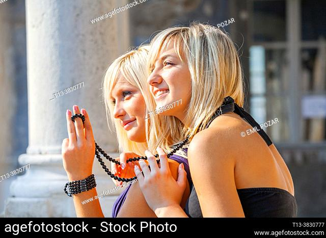 Two blondes teenage girls are flirting with boys by waving a hand