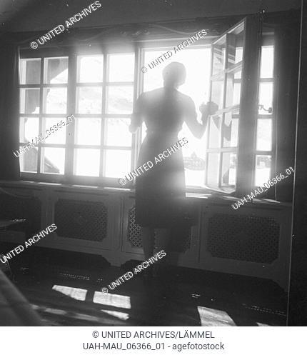 Eine junge Frau blick aus dem Fenster eines Hotels in Zürs am Arlberg, Deutsches Reich 1930er Jahre. A young woman at the window of a hotel with view to...