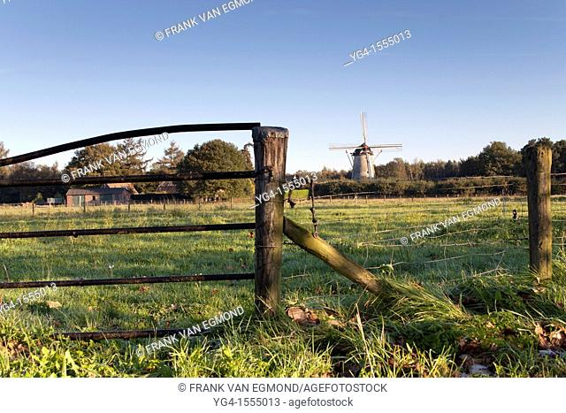 Rural Dutch lanscape with rustic fence and windmill. Hernen, The Netherlands