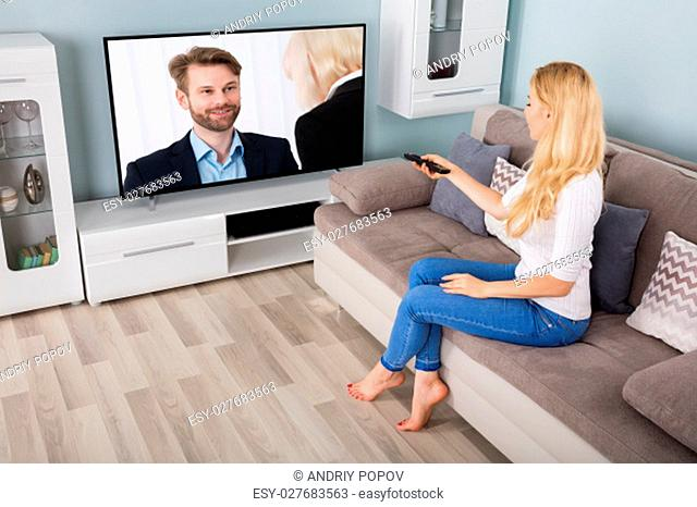 Young Woman On Sofa Watching Movie On Television