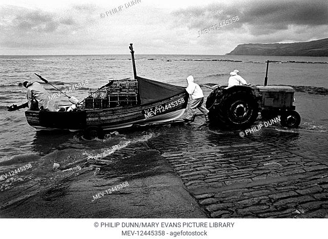 Using an old farm tractor, three fishermen wearing oilskins launch a small lobster boat down the wet cobble slip of Robin Hood's Bay, North Yorkshire