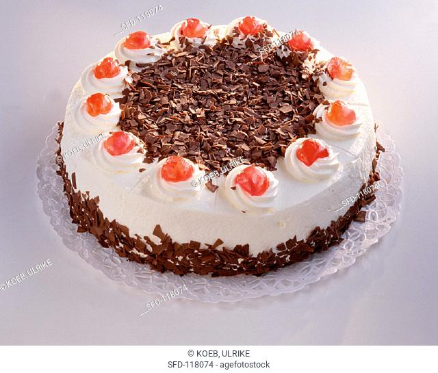 A Black Forest cherry gateau against white background