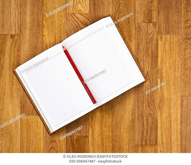 Blank notepad with office supplies on wooden table. Above view